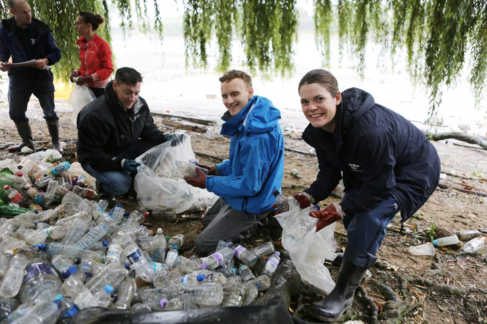 volunteers at the side of the Thames putting recovered plastic bottles into rubbish bags